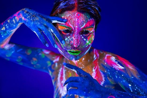 Arte corporal brilhando na luz ultravioleta. arte corporal no corpo e na mão de uma garota brilhando na luz ultravioleta