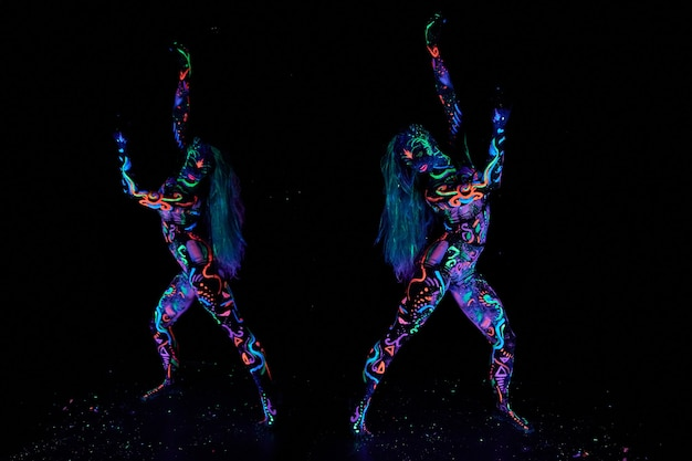 Arte corporal da mulher no corpo dançando na luz ultravioleta. desenhos abstratos brilhantes na cor do néon do corpo da mulher. cabelo e rosto coloridos. ruído, fora de foco
