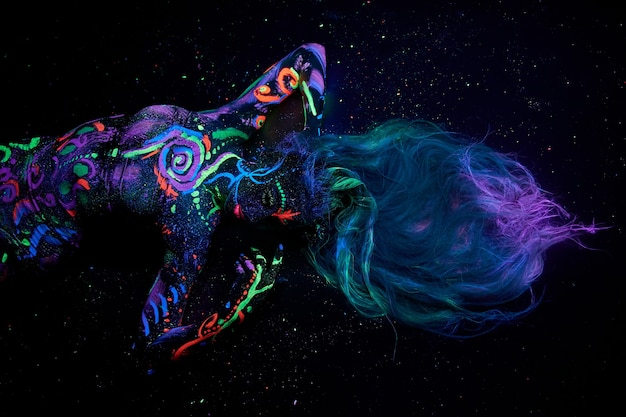 Arte corporal da mulher no corpo dançando na luz ultravioleta. desenhos abstratos brilhantes na cor neon do corpo da menina