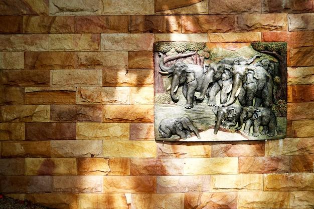 Arte da família do elefante no arenito na parede de pedra do granito