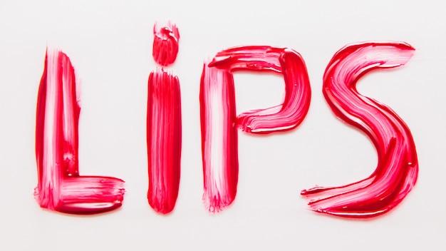 Arte da maquiagem. cosméticos decorativos. brilho manchado de vermelho carmesim. letras de lábios. fundo branco.