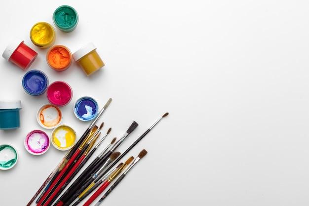 Arte da pintura. conjunto de pintura: pincéis, tintas, tinta acrílica sobre fundo branco