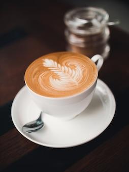 Arte de café com leite no café com a mão da mulher