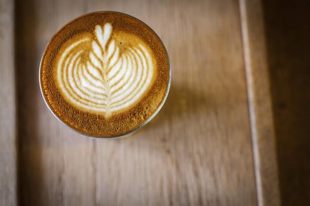 Arte de café com leite sobre a mesa de madeira na cafeteria