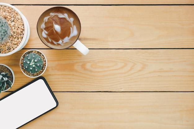 Arte de cappuccino quente e telefone inteligente e cacto na mesa de madeira, vista superior