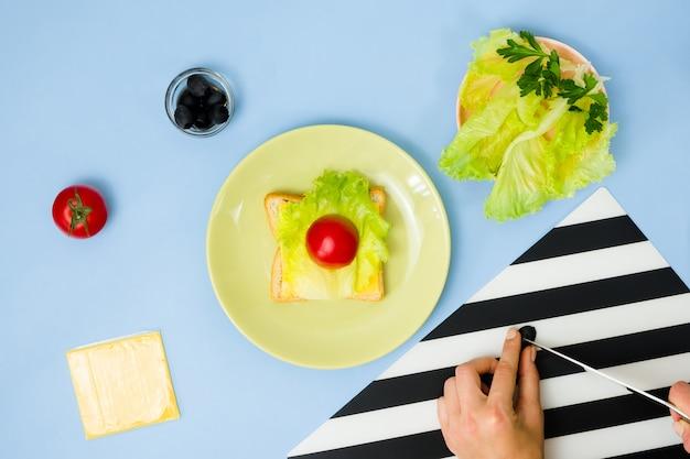 Arte de comida divertida para crianças. sanduíche de joaninha na parede azul. como fazer café da manhã criativo para criança em casa. instruções passo a passo, vista de cima.