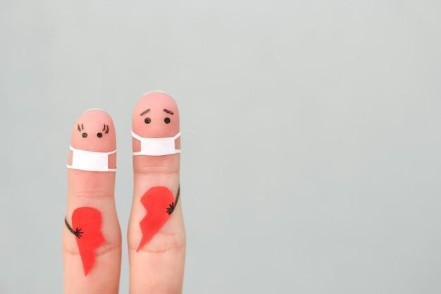 Arte de dedos de casal em máscara médica de covid-2019. conceito de casal segurando um coração partido.