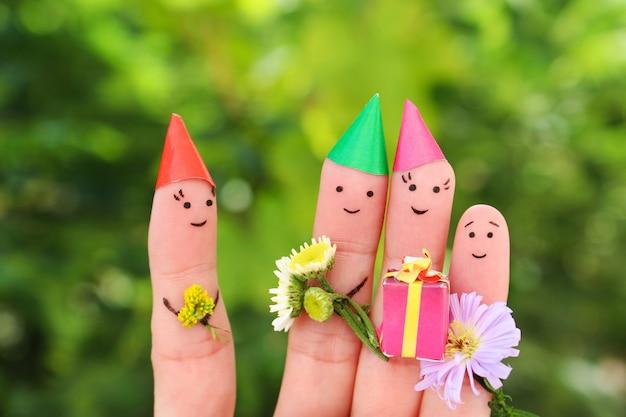 Arte de dedos de pessoas comemora aniversário. conceito de família dá presentes para a mãe.