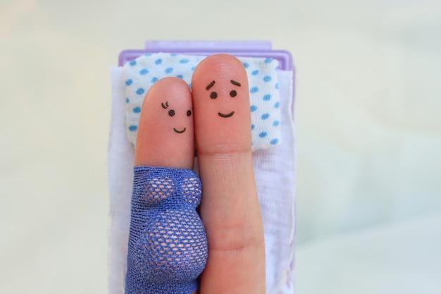 Arte de dedos de um casal feliz dormindo na cama. conceito de sexo durante a gravidez.
