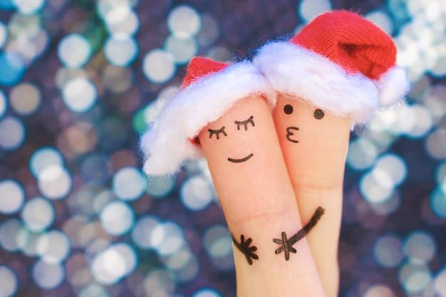 Arte de dedos do casal comemora o natal. conceito de homem e mulher abraço em chapéus de ano novo.