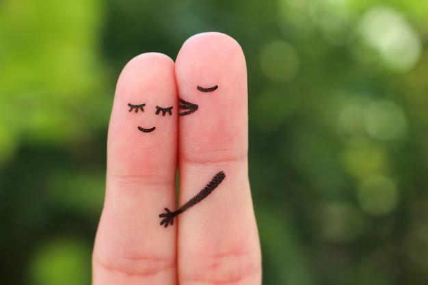 Arte de dedos do casal feliz. homem beija mulher na bochecha.