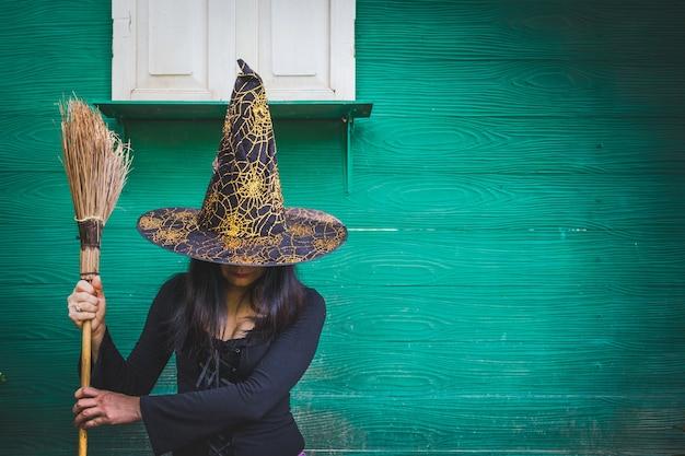 Arte de halloween design, mulher jovem e bonita no chapéu de bruxas e vassoura na mão