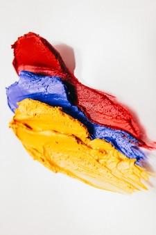 Arte de maquiagem. cosméticos decorativos. amostras de batom vermelho azul amarelo em fundo branco.