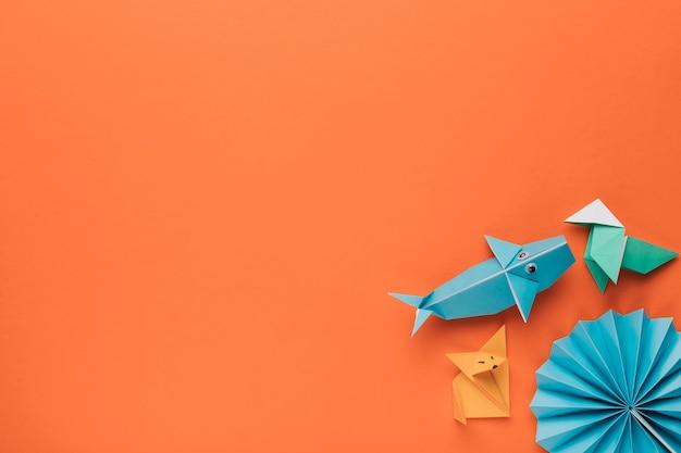 Arte de origami decorativa criativa na esquina do pano de fundo laranja