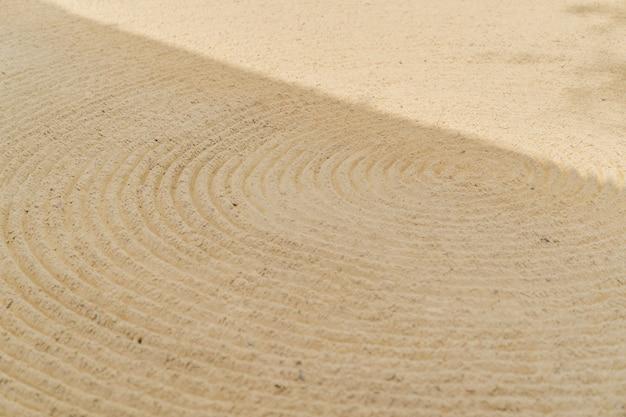 Arte de padrão de onda de curva contínua no fundo de areia.