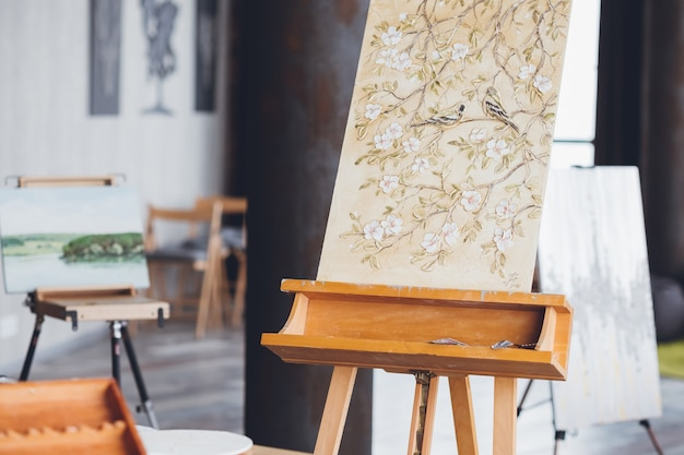 Arte de padrão floral. talento e imaginação do artista. tela sobre cavalete. flores e pássaros. espaço de trabalho do estúdio de arte.