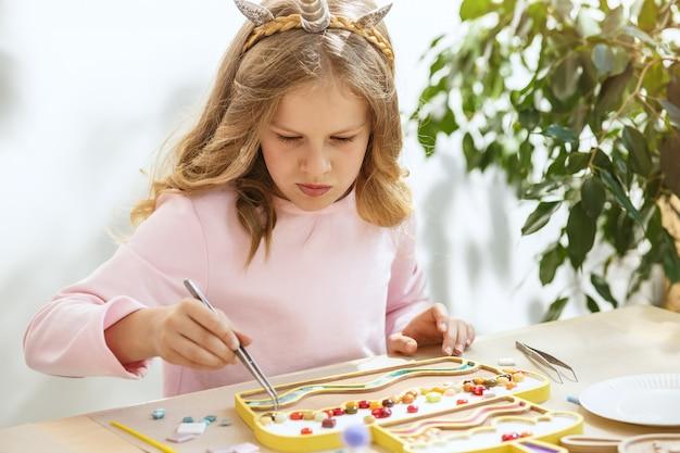 Arte de quebra-cabeça de mosaico para crianças, jogo criativo infantil. duas irmãs estão jogando mosaico