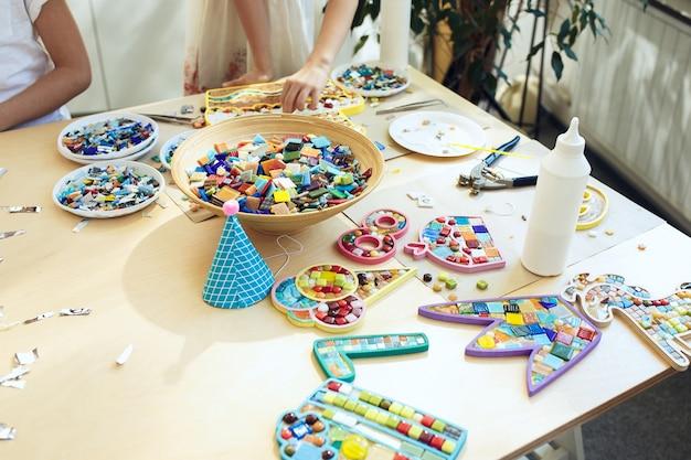 Arte de quebra-cabeça de mosaico para crianças, jogo criativo infantil. mãos estão jogando mosaico na mesa. detalhes coloridos multicoloridos close-up.