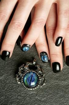Arte de unha fantasia escura em close-up de mãos bem cuidadas