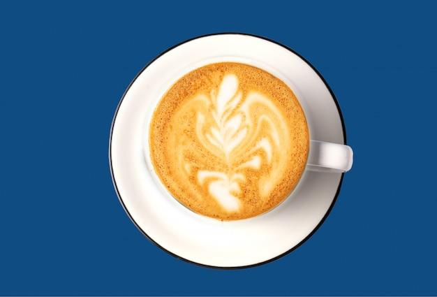 Arte do café com leite no copo branco sobre a cor azul clássica.