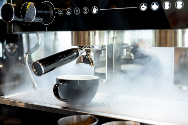 Arte do latte do copo de café colocada no vapor da máquina da cafeteira no café da cafetaria