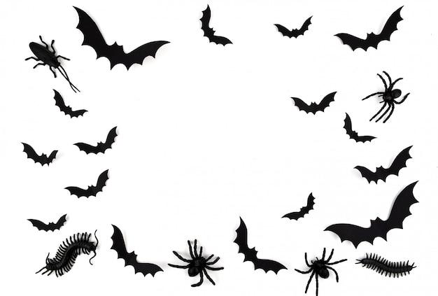 Arte em papel de halloween. morcegos de papel preto voando, besouros e aranhas em branco.