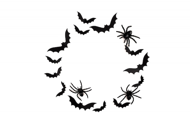 Arte em papel de halloween. morcegos de papel preto voando e aranhas em branco.
