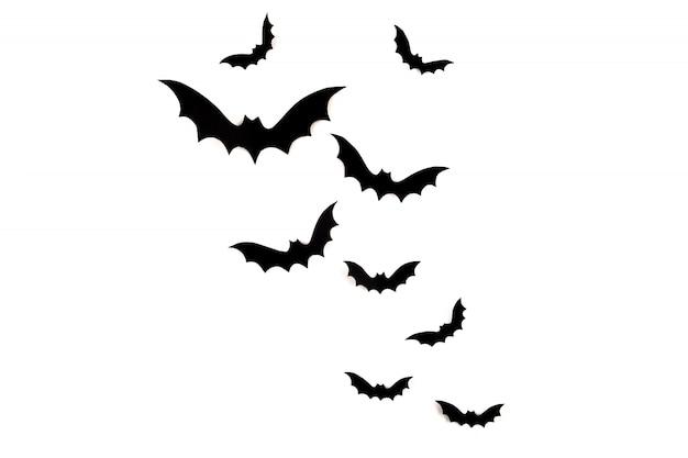 Arte em papel de halloween. morcegos de papel preto voando em branco