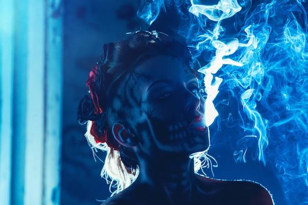 Arte facial de caveira no rosto de uma mulher com fumaça ao ar livre