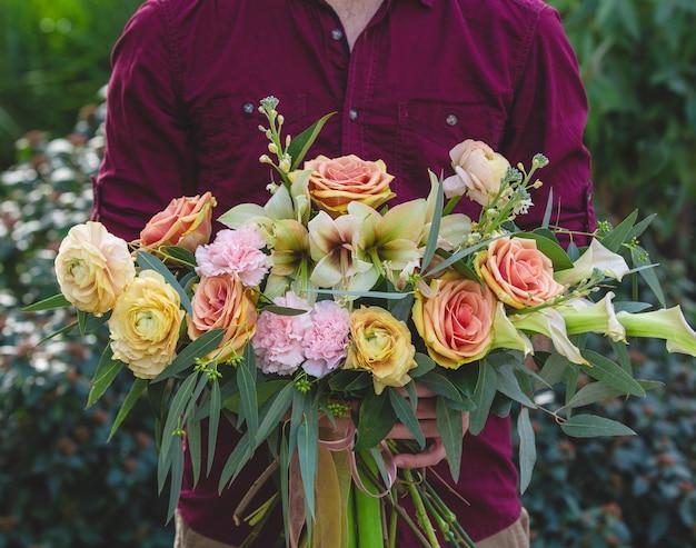 Arte floral, coroa de flores misturadas nas mãos de um homem