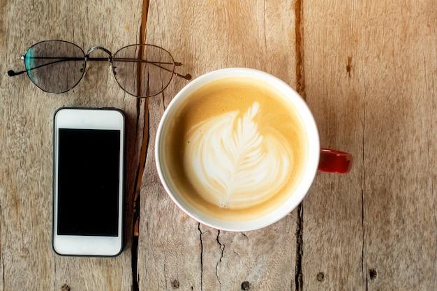 Arte latte quente com telefone inteligente na madeira