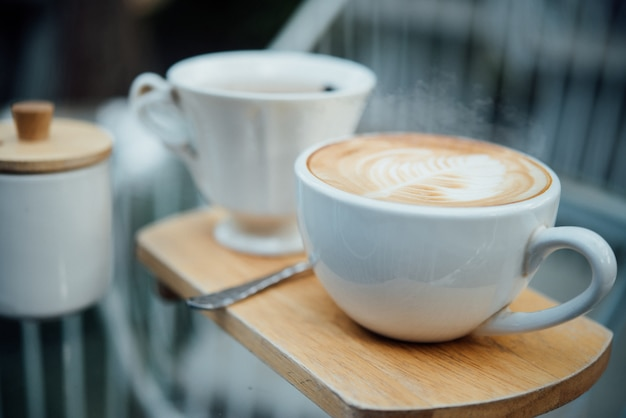 Arte latte quente na xícara de café na mesa de madeira na cafeteria