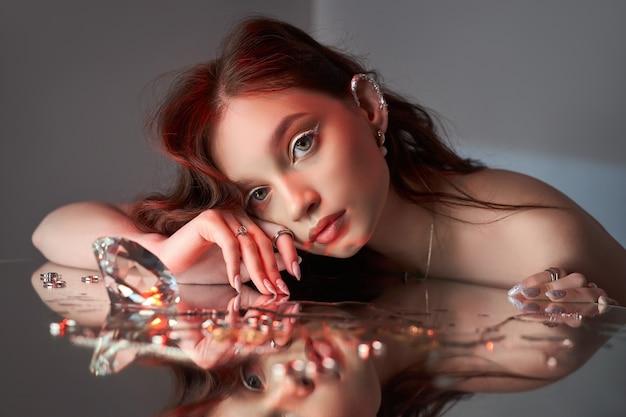 Arte, mulher bonita com maquiagem criativa está deitada no espelho. retrato da beleza de uma mulher romântica com joias