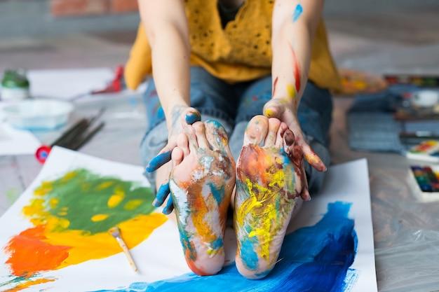 Arte terapia. foto recortada do artista sentado no chão, mostrando os pés e as mãos sujas com tinta multicolor. desfocar o fundo.