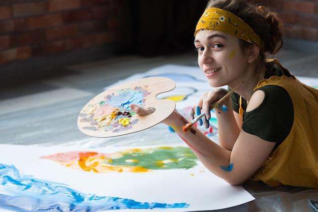 Arte terapia. retrato de uma talentosa pintora deitada no chão, segurando a paleta, criando arte abstrata.