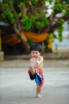 Artes marciais de muay thai, boxe tailandês tailândia, menino bonito do retrato ao ar livre.