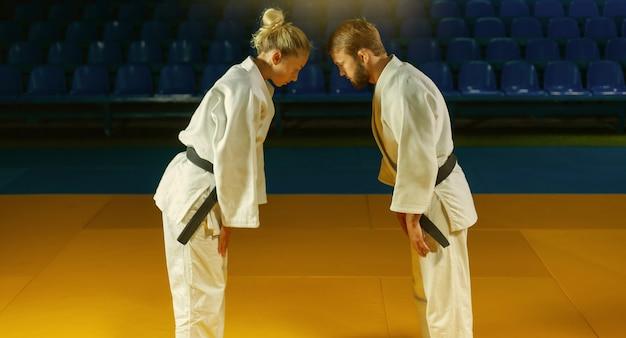 Artes marciais. poupando portners. homem e mulher do esporte se cumprimentam antes de uma luta no pavilhão esportivo