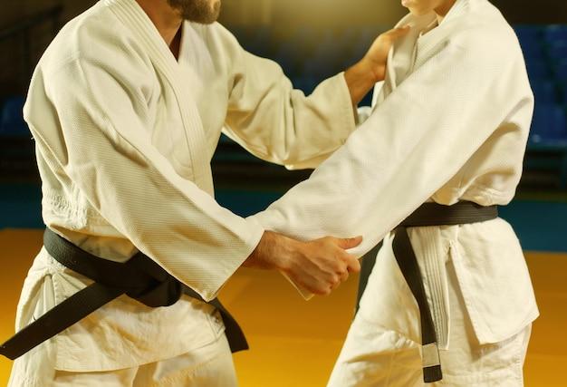 Artes marciais. poupando portners. o homem e a mulher do esporte no quimono branco treinam judô capturas no pavilhão desportivo. cortar foto
