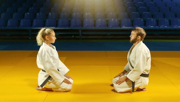Artes marciais. poupando portners. o homem e a mulher do esporte se cumprimentam enquanto estão sentados no ginásio