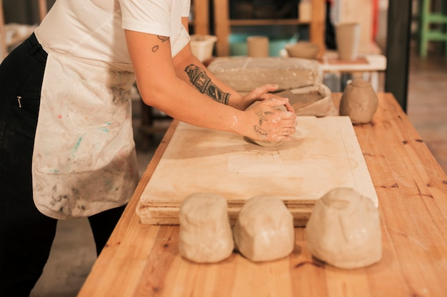 Artesã amassar o barro na placa de madeira sobre a mesa