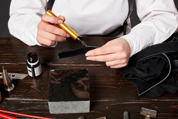 Artesã feminina fazendo bolsa de couro genuíno na mesa