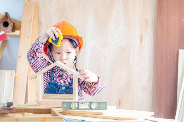 Artesã menina asiática medindo o tamanho do brinquedo de casa de madeira na carpintaria.