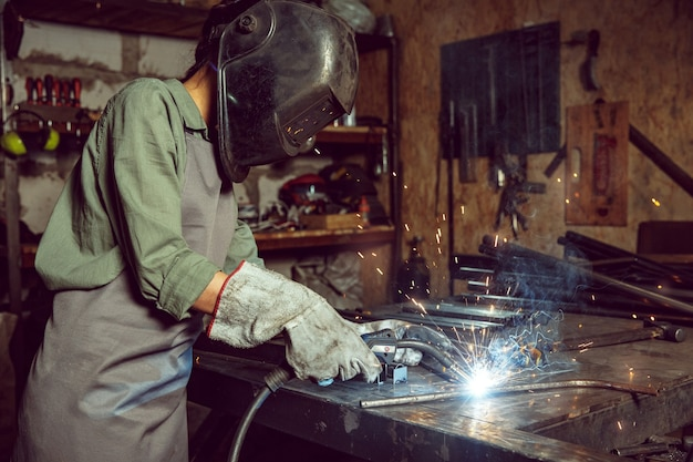 Artesã ocupada e séria, moendo madeiras com máquina especial. mulher bonita usando óculos de segurança. conceito de marcenaria e marcenaria. igualdade de gênero. profissão masculina