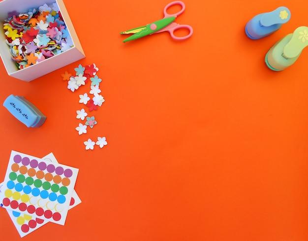 Artesanato com flores de papel, socos, tesouras e adesivos em fundo laranja