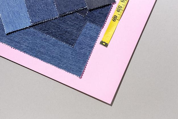 Artesanato, conserto de roupas. acessórios de costura jeans azul rasgado com fundo colorido de cima. postura plana