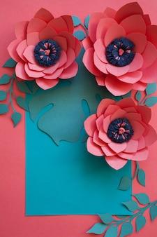 Artesanato criativo quadro floral decorativo feito de flores de papel e folhas, cartão para convite com várias folhas em um azul. configuração plana.