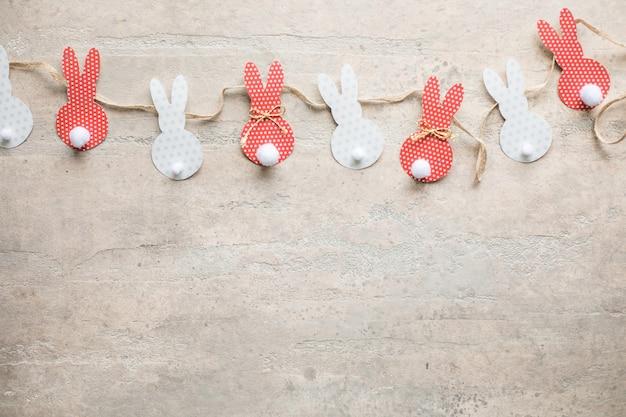 Artesanato de coelhinho da páscoa pom pom. fundo de corte de papel de decoração de coelhinho da páscoa. guirlanda de coelhos coloridos faça você mesmo