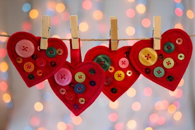 Artesanato de corações de feltro vermelho decorado com miçangas e botões com luzes. decoração dia dos namorados.