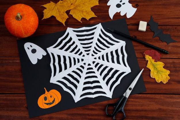 Artesanato de halloween diy. teia de aranha cortada em papel. criatividade infantil.