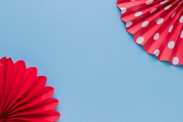 Artesanato de papel origami vermelho decorativo na superfície azul